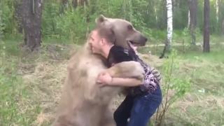 熊と相撲をとる男性
